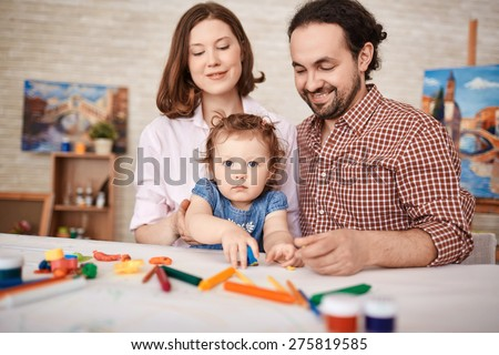 Young parents and pretty daughter playing together - stock photo