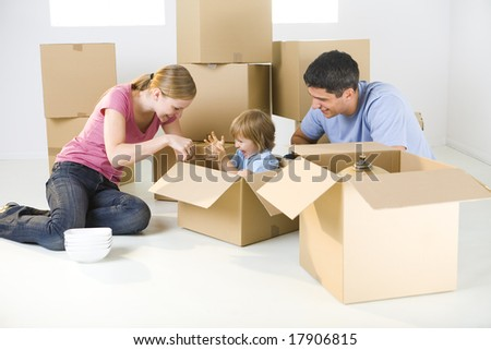 Young parents and their daughter sitting beside cardboard boxes. Young girl sitting in box. - stock photo