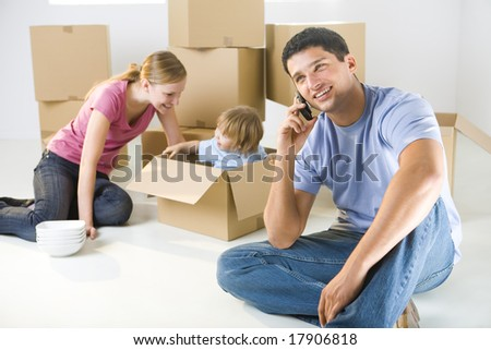 Young parents and their daughter sitting beside cardboard boxes. Young girl sitting in box. They're smiling. A man talking by cellphone. Focused on man.