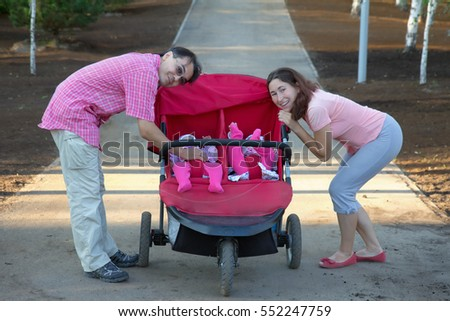 young parents and their two little children in a twin stroller