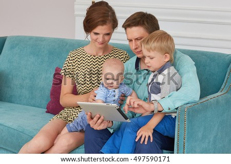 Young parents and two children sit on a sofa in the room with computer tablet. Happy family. Six month and four years. Parenting and early development.