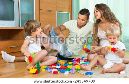 Young parents and two little daughters playing with plastic toys in home. Focus on girl  - stock photo