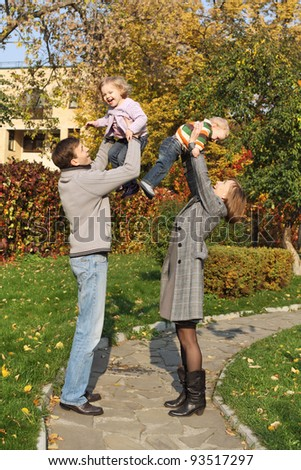 Young parents are having fun with the kids in the park, put one up - stock photo