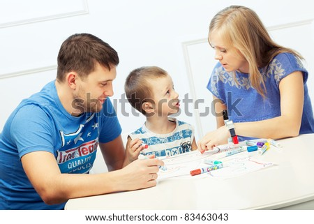 Young parents drawing at the table with their son