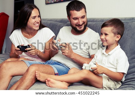 Young parents encourage their small son to play videogame using joysticks while spending fay together