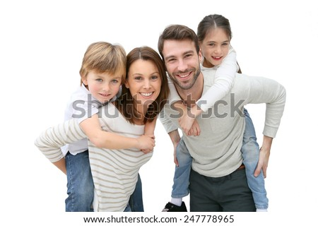 Young parents giving piggyback ride to kids - stock photo