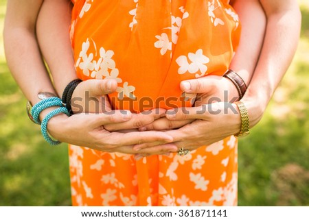young parents hands on the belly of mother in orange dress - stock photo