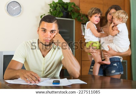 Young parents having conflict in front of children in home interior  - stock photo