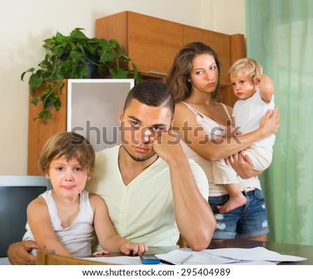 Young parents having quarrel in front of children indoor. Focus on man - stock photo