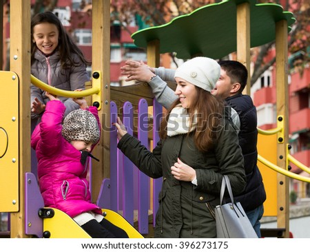 Young parents helping positive little kids on slide in autumn day outdoor. Focus on woman - stock photo