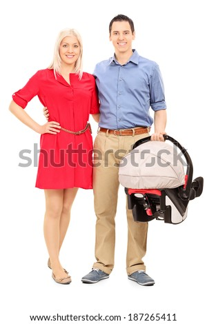 Young parents holding a baby stroller isolated on white background - stock photo