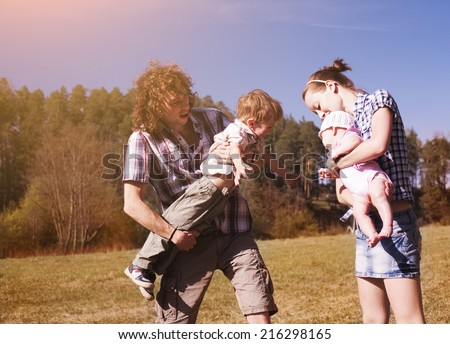 Young parents holding adorable kids playing outdoors- family time - stock photo