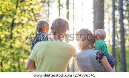 Young parents holding their babies as they enjoy a summer day in the forest facing away from the camera into the rising morning sun between the tree trunks, with sun flare. - stock photo