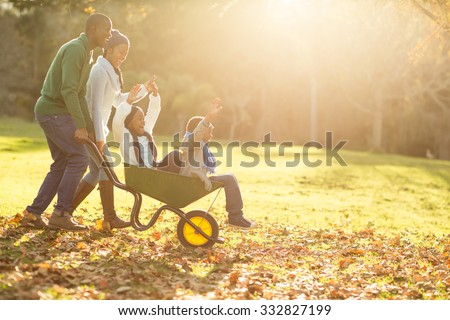 Young parents holding their children in a wheelbarrow on an autumns day