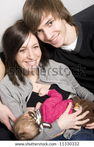 young parents on a sofa with their baby girl