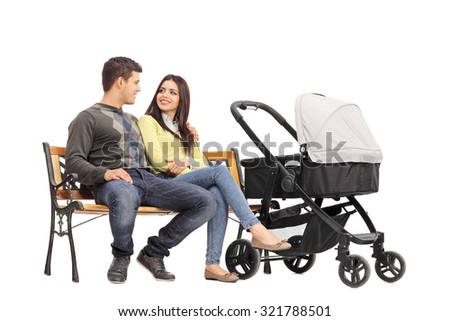 Young parents sitting on a bench and talking to each other with a baby stroller next to them isolated on white background - stock photo