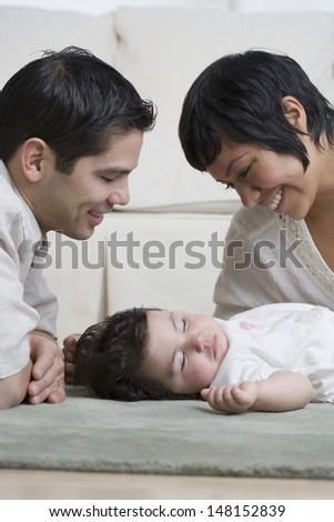 Young parents smiling at baby - stock photo