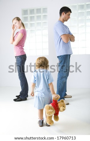 Young parents standing back to back. Theirs daughter holding teddy bear. She's standing back to camera. - stock photo