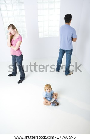 Young parents standing back to back. Theirs daughter sitting on the floor and looking at camera. High angle view. - stock photo