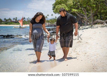Young parents teaching their toddler to walk. They are expecting another child soon. - stock photo