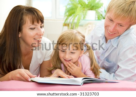 Young parents train the child in reading - stock photo