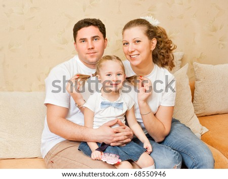Young parents with a daughter at home - stock photo