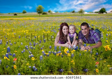 Young parents with baby girl lying in a bluebonnet field. - stock photo