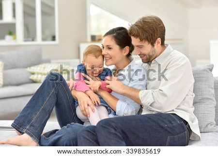 Young parents with baby sitting in sofa at home - stock photo