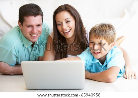 Young parents, with child, on laptop computer