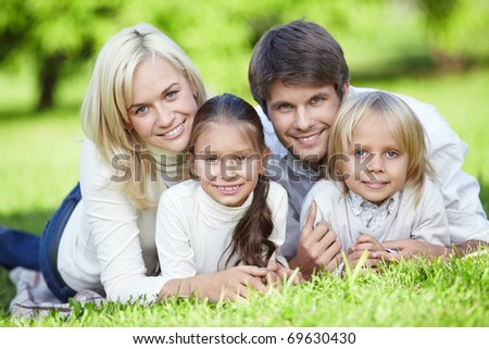 Young parents with children on the grass - stock photo