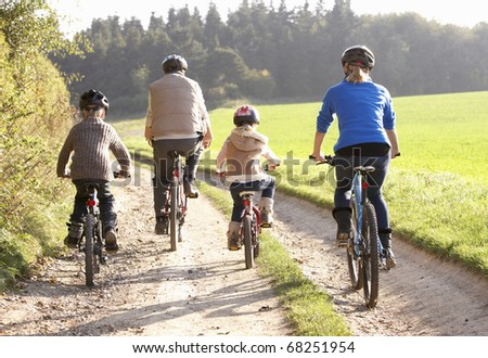 Young parents with children ride bikes in park - stock photo