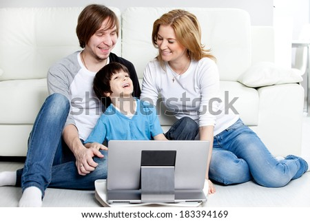 Young parents with children with laptop computer - stock photo