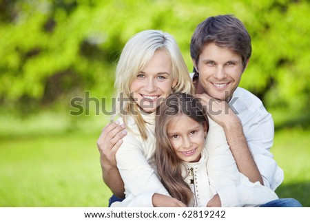 Young parents with daughter outdoors - stock photo