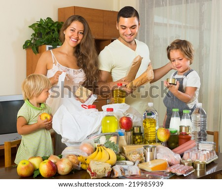 Young parents with female children sorting purchased food out indoor