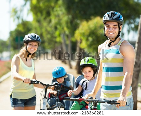 Young parents with kids in baby bicycle seats outdoor