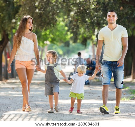 Young parents with little children in park on summer day - stock photo