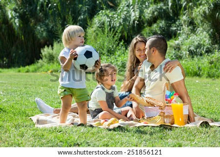 Young parents with little daughters having vacation with picnic - stock photo