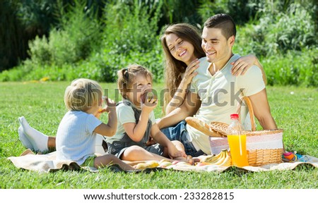 Young parents with little girls having holiday with picnic - stock photo