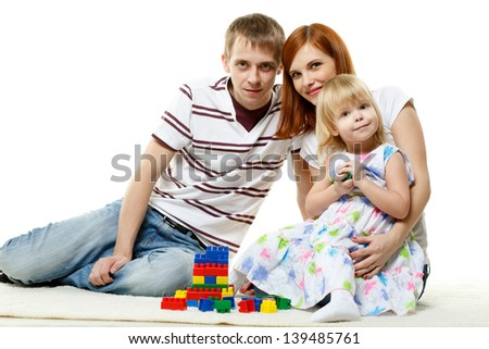 Young parents with lovely daughter build house on a white background.  Concept of  building and purchase  of the house. - stock photo