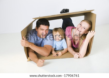 Young parents with their daughter lying in cardboard box. They're smiling and looking at camera. Front view.