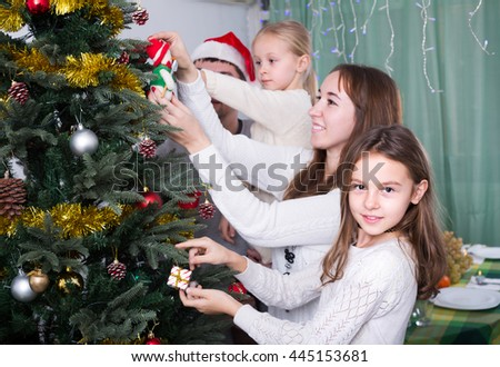 Young parents with two children decorating Christmas tree at home. Focus on girl - stock photo