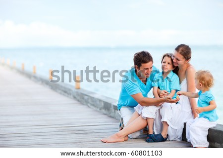 Young parents with two kids sitting on jetty - stock photo