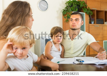 Young parents with two little daughters having conflict in home interior  - stock photo