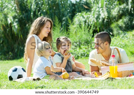 Young parents with two  little daughters having holiday with picnic - stock photo