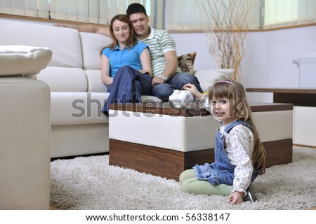 young parrents at home with beautiful child make savings and put coins money in piggy bank - stock photo