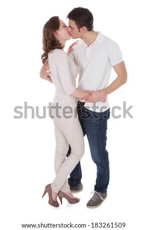 Young passionate couple in casuals kissing each other isolated over white background - stock photo