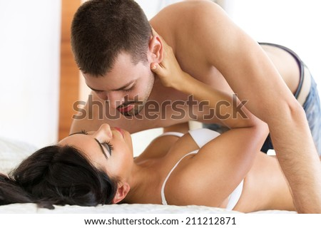 Young passionate couple in their bedroom  - stock photo