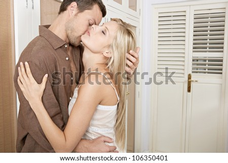 Young passionate couple kissing in a home's bedroom. - stock photo