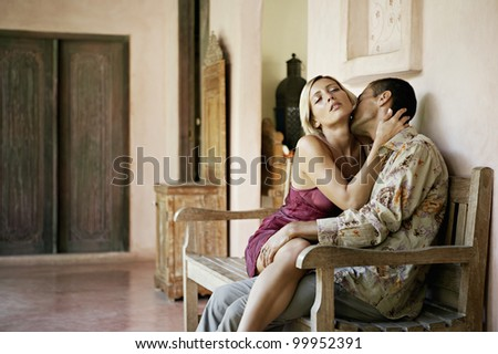 Young passionate couple kissing on a bench. - stock photo