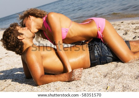 Young passionate couple kissing on the sand - stock photo